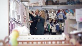 Une jeune femme enceinte heureuse choisit des vêtements pour un nouveau-né dans un magasin du ` s d'enfants banque de vidéos