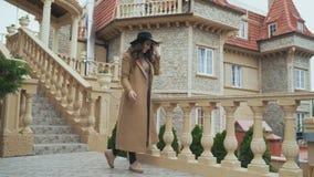 Une jeune femme européenne élégante, avec les cheveux bouclés et le chapeau à la mode, attend quelqu'un sur le balcon de banque de vidéos