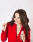 Une jeune femme garde une bouteille en verre de sérum de cheveux Images libres de droits