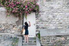 Une jeune femme inconnue sélectionne une rose d'un mur de jardin Image stock