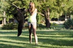 Une jeune femme jouant avec son chien Photos stock