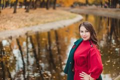 Une jeune femme marche en parc d'automne Femme de brune portant un manteau vert et une robe rouge photos stock