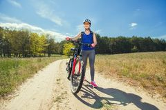 Une jeune femme monte sur un vélo de montagne en dehors de ville sur la route dans la forêt Photographie stock