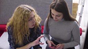 Une jeune femme montre ses croquis et idées à un ami dans l'atelier clips vidéos