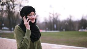 Une jeune femme musulmane dans un foulard traditionnel causant avec des amis sur un smartphone en parc, une dame marche le long banque de vidéos