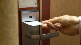 Une jeune femme ouvre la porte de sa chambre d'hôtel utilisant une carte principale électronique banque de vidéos