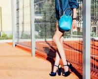 Une jeune femme posant dans un équipement de jeans, les chaussures à talons hauts incroyables et un sac à main bleu superbe-façon Photo stock