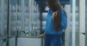 Une jeune femme pour ouvrir la porte de réfrigérateur pour stocker des appareils et pour rivaliser avec d'autres modèles pour ach banque de vidéos