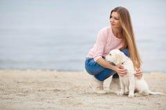 Une jeune femme près de la mer avec un chien d'arrêt de chiot Image libre de droits