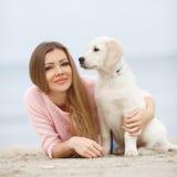 Une jeune femme près de la mer avec un chien d'arrêt de chiot Photos libres de droits
