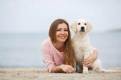 Une jeune femme près de la mer avec un chien d'arrêt de chiot Photographie stock