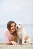 Une jeune femme près de la mer avec un chien d'arrêt de chiot Photos stock