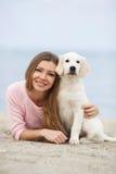 Une jeune femme près de la mer avec un chien d'arrêt de chiot Image stock