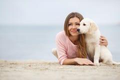 Une jeune femme près de la mer avec un chien d'arrêt de chiot Photographie stock libre de droits