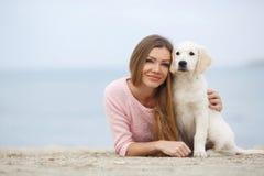 Une jeune femme près de la mer avec un chien d'arrêt de chiot Images stock