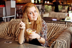 Une jeune femme prenant le déjeuner à rire de café Image libre de droits