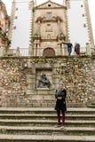 Une jeune femme prend une photo avec un bâton de selfie dans la plaza de San Jorge, vieille ville à l'arrière-plan, Caceres, Espa images libres de droits