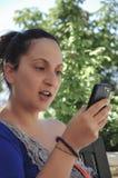 Une jeune femme regardant quelque chose à un téléphone intelligent images libres de droits