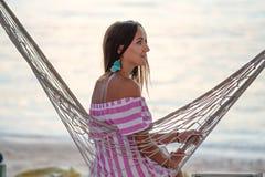 Une jeune femme regarde au côté, se reposant dans un hamac sur la plage photos libres de droits