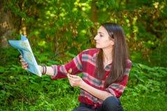 Une jeune femme regarde une carte tout en augmentant Photographie stock libre de droits