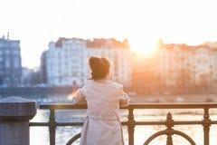 Une jeune femme regarde le coucher du soleil Image libre de droits