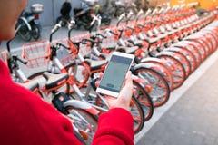 Une jeune femme regarde le téléphone intelligent pour trouver sa bicyclette image libre de droits