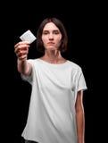 Une jeune femme sérieuse montrant un préservatif emballé sur un fond noir Concept sain de style de vie Copiez l'espace Photo stock
