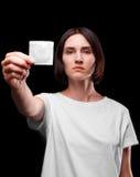 Une jeune femme sérieuse montrant un préservatif emballé sur un fond noir Concept sain de style de vie Copiez l'espace aides Photos stock