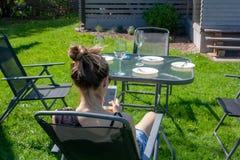 Une jeune femme s'assied dans un jardin avec un t?l?phone dans des ses mains Du dos image stock