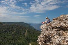 Une jeune femme s'assied sur une montagne et regarde une belle vue Photographie stock