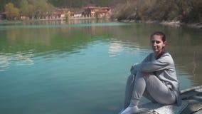 Une jeune femme s'assied sur un vieux bateau par le lac une journée de printemps, détendant en nature La cam?ra va de bas en haut banque de vidéos