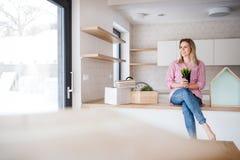 Une jeune femme se déplaçant la nouvelle maison, se reposant sur un compteur dans la cuisine image libre de droits