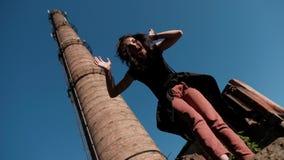 Une jeune femme se tient contre la pile d'usine et désorganise joyeux ses cheveux de la vue ci-dessous banque de vidéos