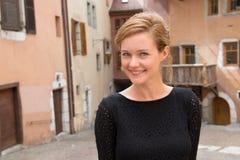 Une jeune femme se tient et sourit Images libres de droits
