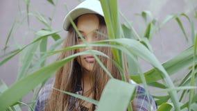 Une jeune femme se tient parmi l'herbe grande S banque de vidéos