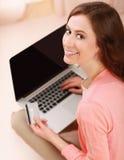 Une jeune femme se trouvant sur le plancher avec un ordinateur portable Photos libres de droits