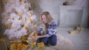 Une jeune femme secoue des cadeaux de Noël banque de vidéos