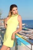 Une jeune femme sensuelle posant dans une robe jaune Une fille attirante sur un fond de ciel bleu Une dame sexy des vacances d'ét photos stock