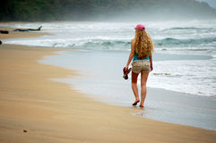 Une jeune femme seul marche sur la plage Image libre de droits