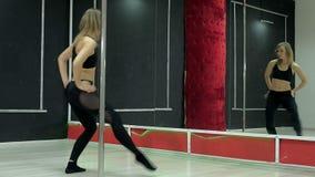Une jeune femme sexy sexy de danse, une poly danse de danse dans le hall autour du poteau Photos libres de droits