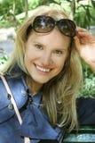 Une jeune femme souriant sur un banc de stationnement Photographie stock libre de droits
