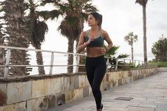 Une jeune femme sportive courant le long de la promenade photos stock
