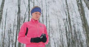 Une jeune femme sur l'essai de matin se tient dans des ses mains qu'un smartphone sélectionne une voie de musique pour la formati banque de vidéos