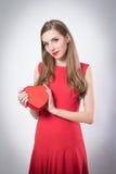 Une jeune femme tenant un grand coeur rouge Image stock