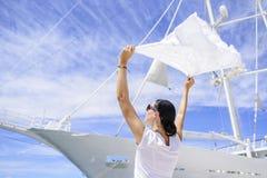 Une jeune femme tient une écharpe vent-éraflée dans le vent sur un fond blanc du ` s de bateau Photo stock