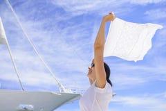 Une jeune femme tient une écharpe vent-éraflée dans le vent sur un fond blanc du ` s de bateau Images libres de droits
