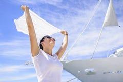 Une jeune femme tient une écharpe vent-éraflée dans le vent sur un fond blanc du ` s de bateau Photos libres de droits