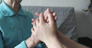 Une jeune femme tient les mains froissées d'une vieille grand-mère banque de vidéos