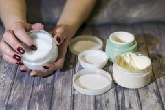 Une jeune femme tient un pot de crème images stock