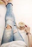 Une jeune femme utilisant les jeans affligés se reposant sur le plancher en bois sur un tapis blanc de fourrure à la maison et de Photo stock